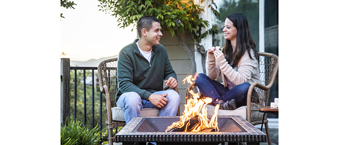 Stacked DURAFLAME® OUTDOOR FIRELOGS burning in firepit with couple smiling at each other