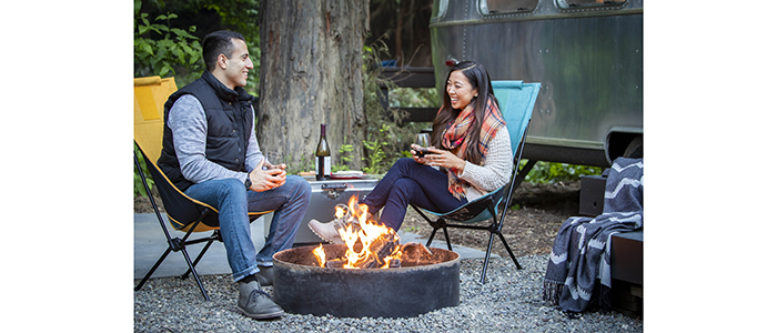 Glamping with Airstream in background and couple enjoying DURAFLAME® OUTDOOR FIRELOGS burning in campfire pit