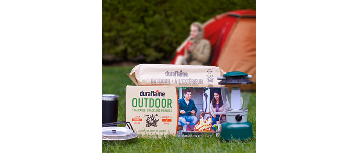 Camper and Tent in background with case of DURAFLAME® OUTDOOR FIRELOGS for CAMPING