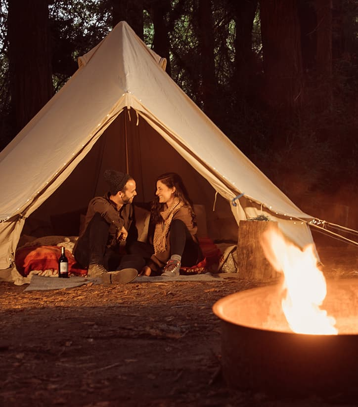 Couple glamping sitting in a tent with duraflame fire in foreground