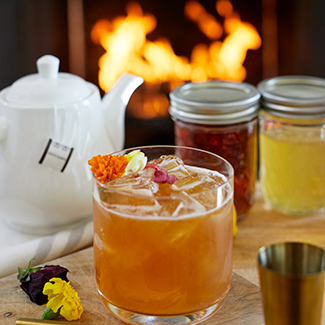 Earl Grey Cocktail with floral garnish and duraflame fire burning in backgroun