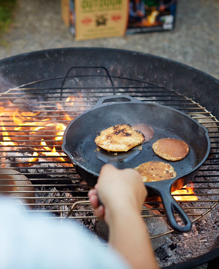 Person flipping pancakes in a griddle over campfire of burning duraflame OUTDOOR firelogs