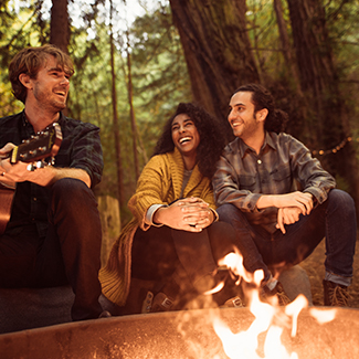 Friends laughing as one plays guitar sitting at a campfire in the woods
