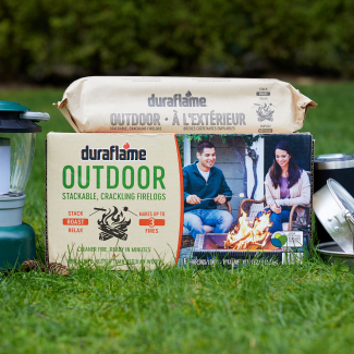 Duraflame OUTDOOR firelog case and log packaging on lawn with camping gear