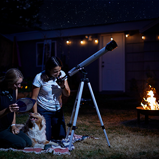 People on blanket with dog stargazing through telescope while fire pit fire burns in background