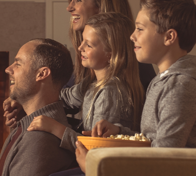 Family sitting on couch fireside with popcorn laughing watching a movie