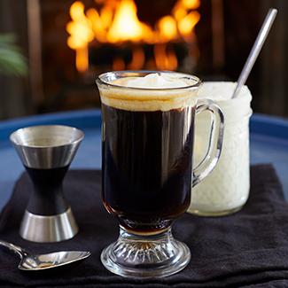 Irish Coffee with duraflame fire burning in backgroun