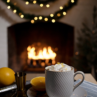 Spiked Orange hot chocolate in mug with duraflame fire burning in background