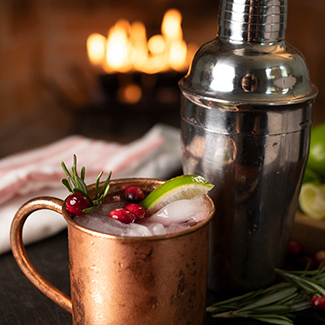 Cranberry Moscow Mule in copper mug with duraflame fire burning in background