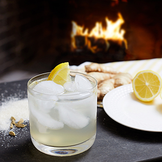 Lemon Ginger Mocktail with lemon garnish and duraflame fire burning in background