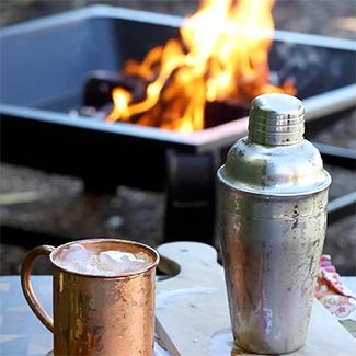 Pumpkin & Apple Cider Fizz in copper mug with duraflame fire  burning in a fire pit in background