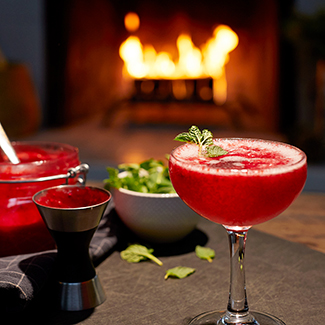 Raspberry bellini with duraflame fire burning in background