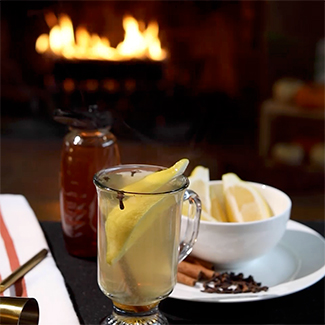 Hot Toddy garnished with lemon and cloves with duraflame fire burning in background